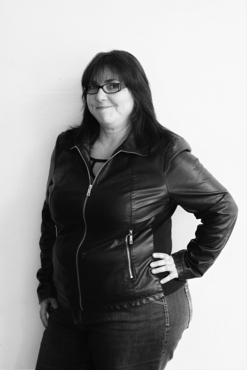 Christine standing smiling leather jacket bw